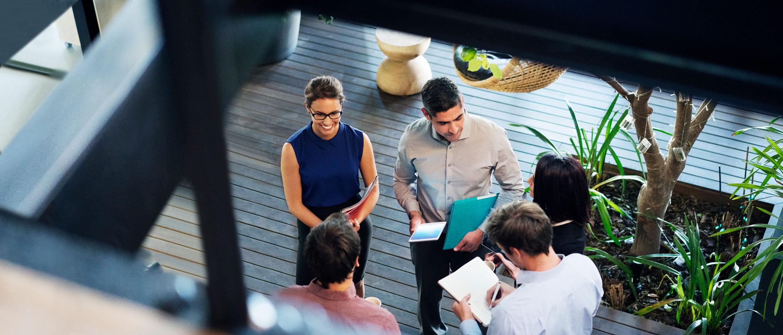 Pet zaposlenih (dve ženski in trije moški) na delovnem mestu prihodnosti imajo neformalni poslovni sestanek v pisarni. Prizor je prikazan od zgoraj. Med sestankom imajo v rokah dokumente, beležnice in tablične računalnike.