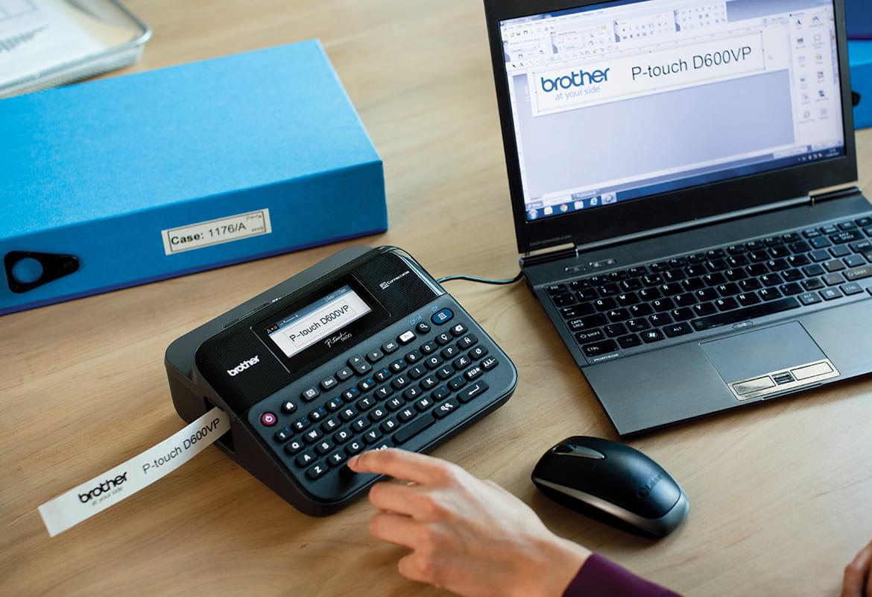 Tiskalnik nalepk P-touch na pisarniški mizi, povezan s prenosnikom, tiska nalepko