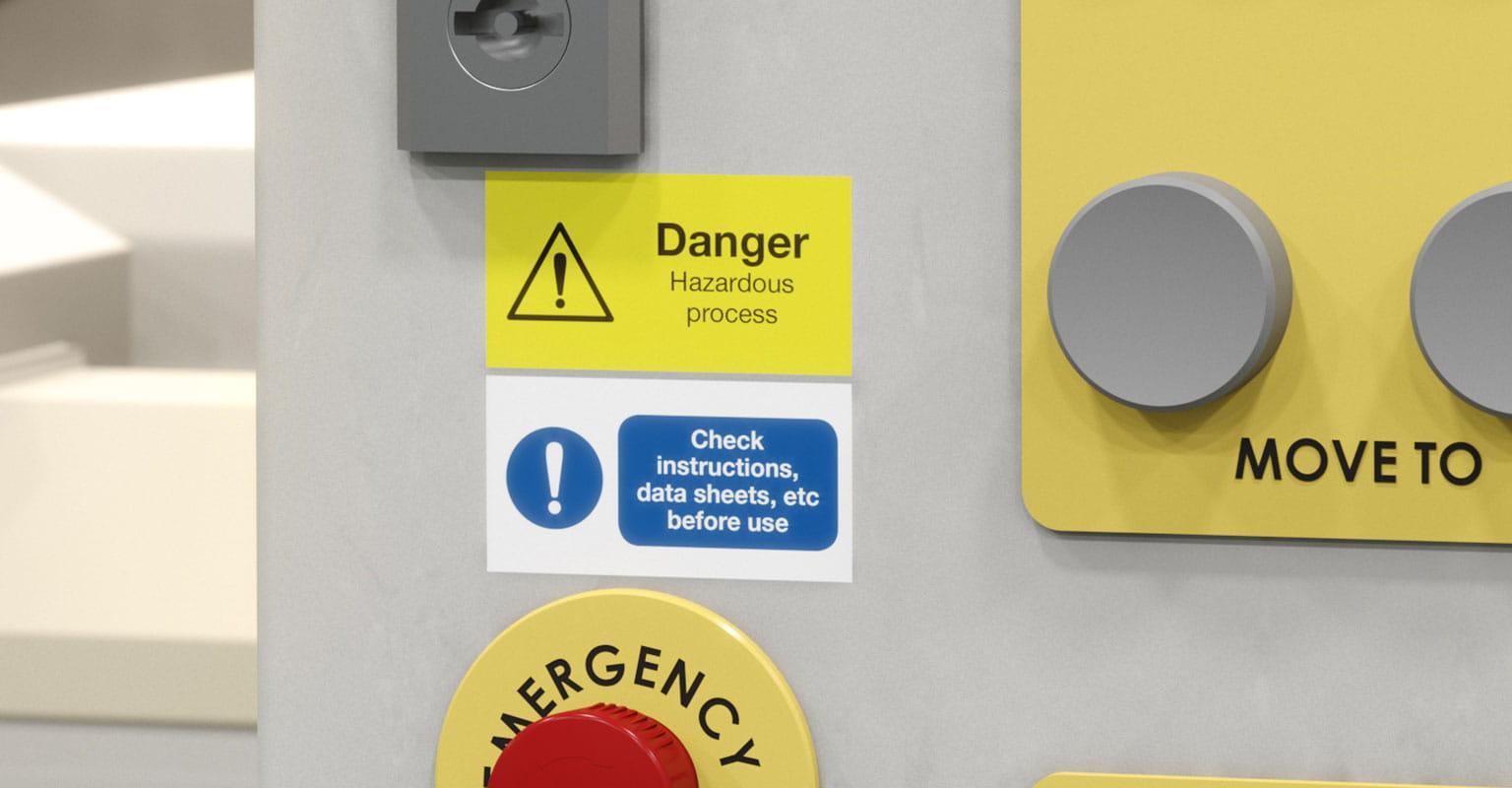 Dve nalepki Brother P-touch na nadzorni plošči, opozorilo na nevarnost in pred uporabo preberite navodila