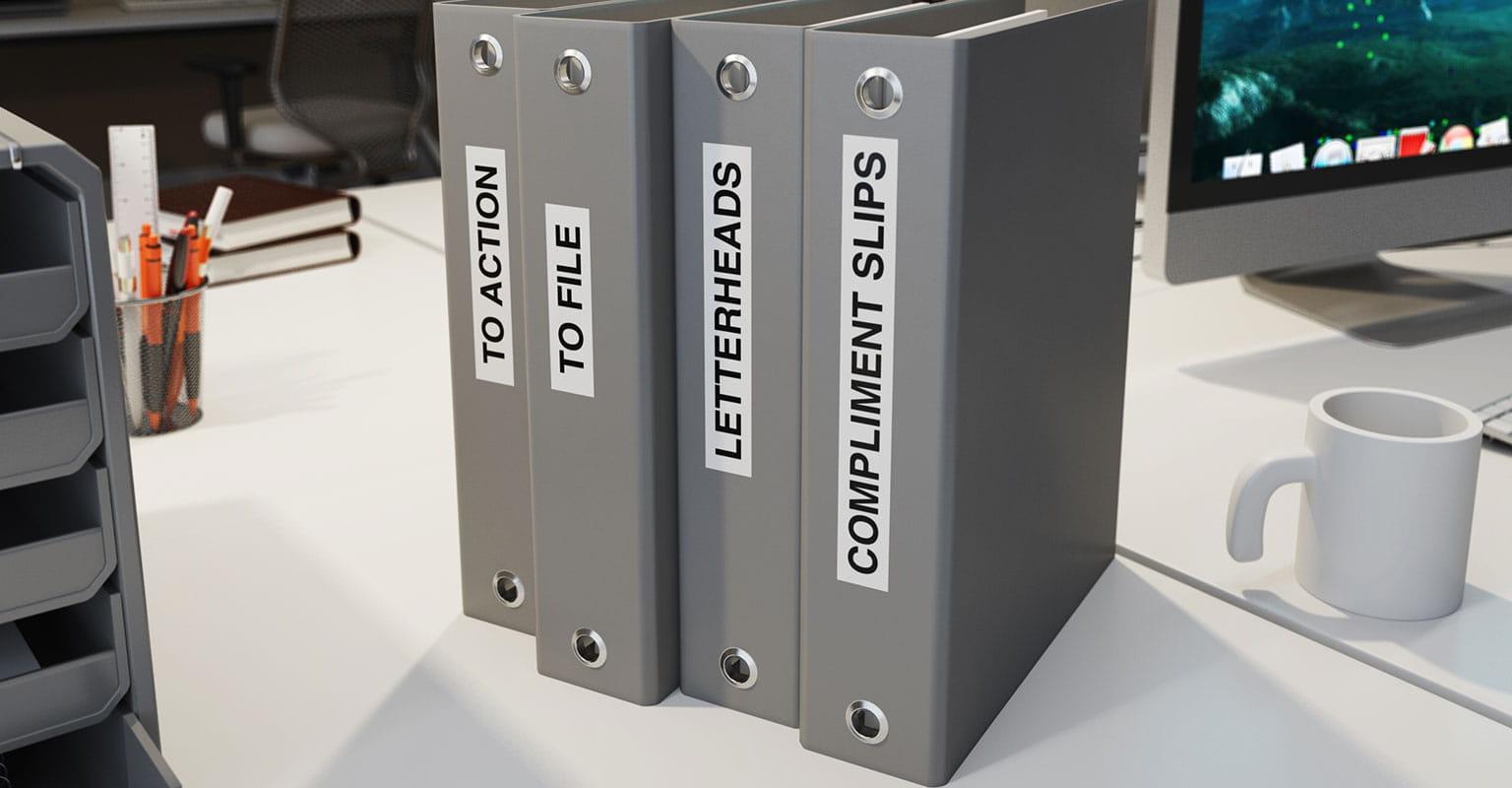 Štirje fascikli z nalepkami Brother P-touch na hrbtišču, ki označujejo vsebino fasciklov