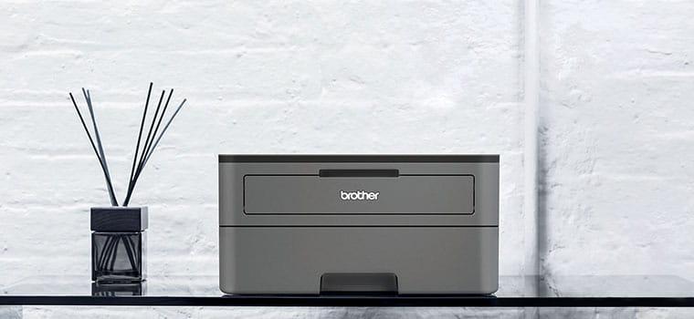 Temno siv črno-beli laserski tiskalnik HL-2350DW na stekleni mizi z osvežilcem zraka