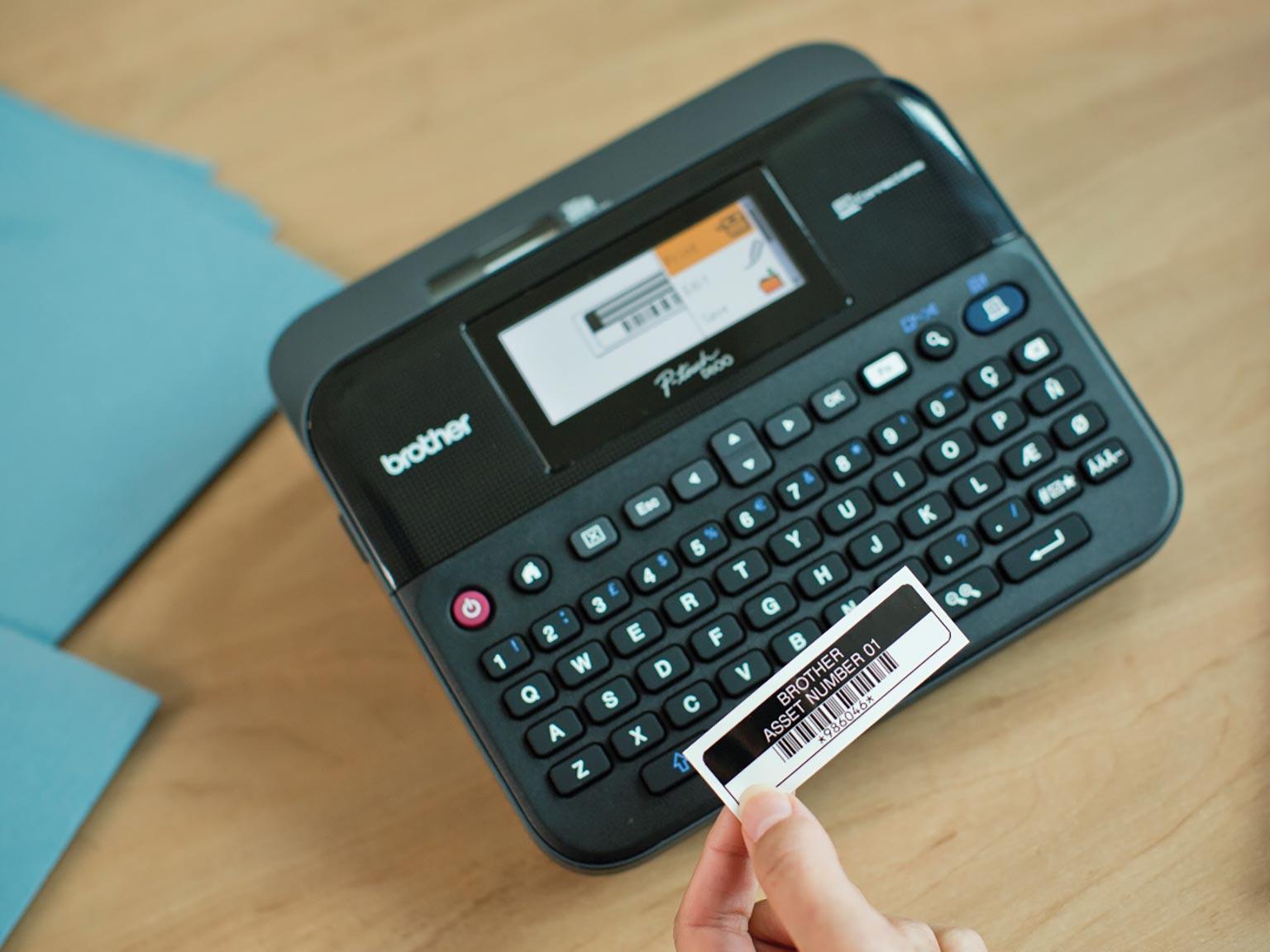 Tiskalnik nalepk Brother P-touch D600 z roko, ki drži nalepko za inventar
