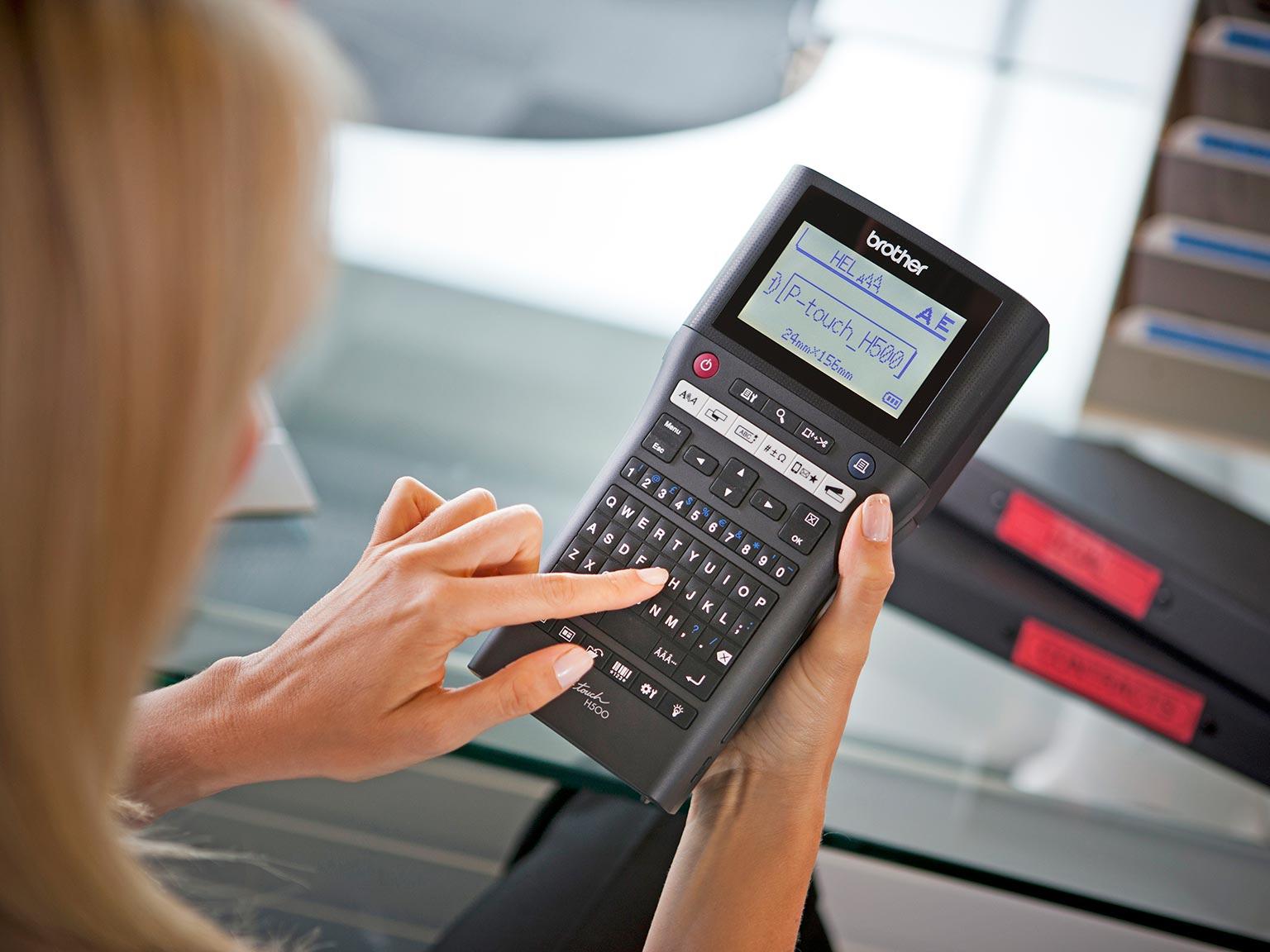 Tiskalnik nalepk P-touch H500 tiska nalepko, medtem ko ga drži v roki upravitelja objektov