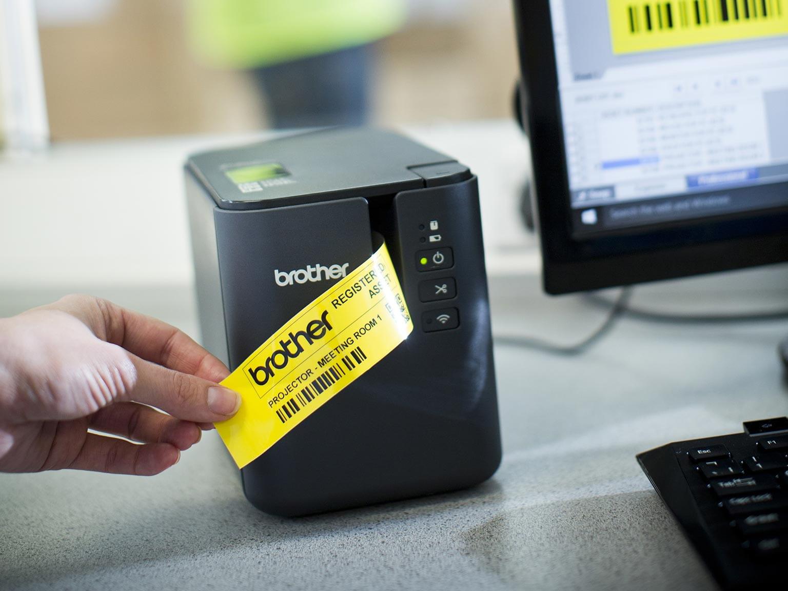 Tiskalnik nalepk Brother P-touch P900W z rumeno nalepko, ki se tiska z računalnika