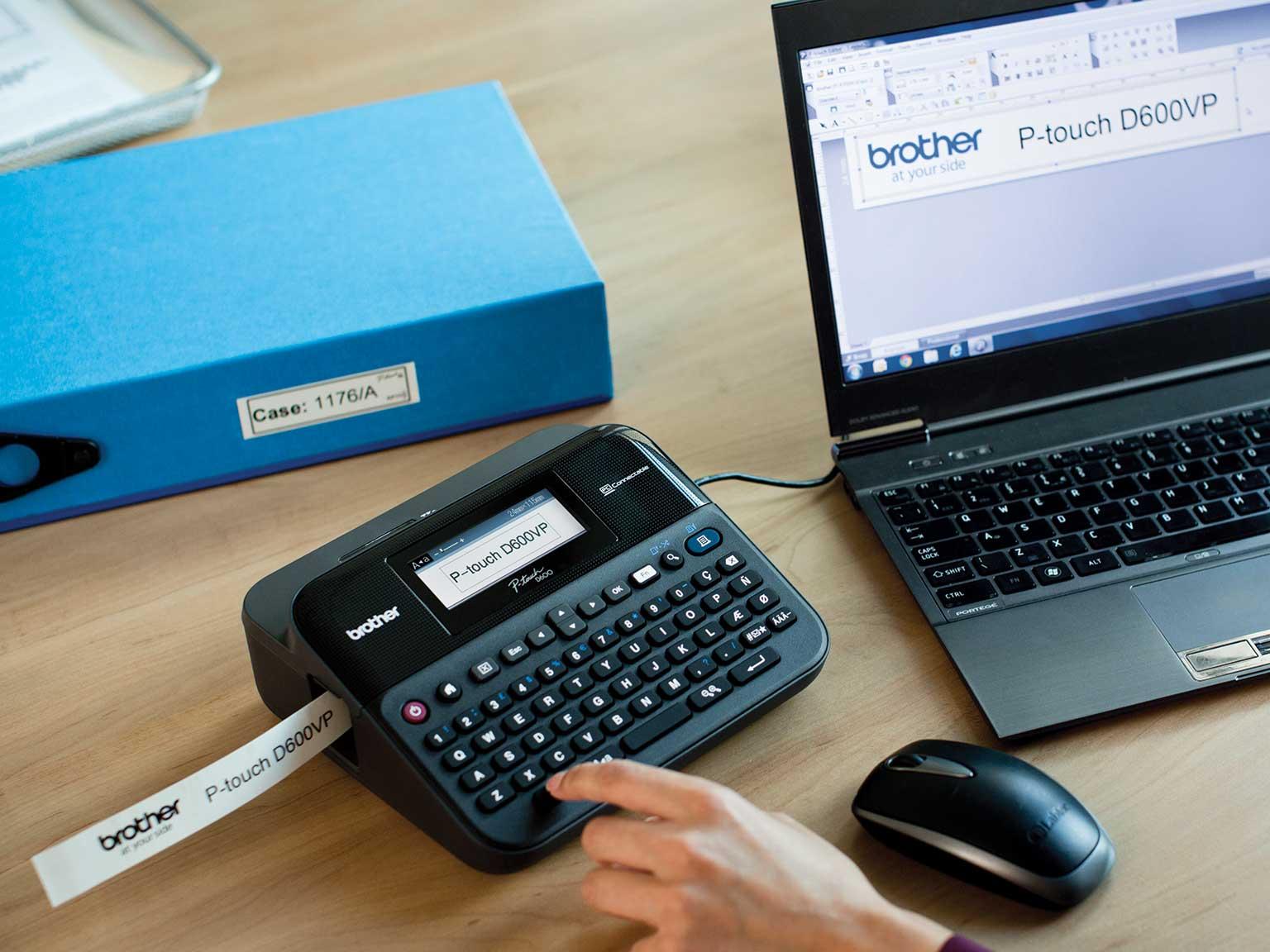 tiskalnik obstojnih nalepk P-touch na pisarniški mizi, priključeni na računalnik