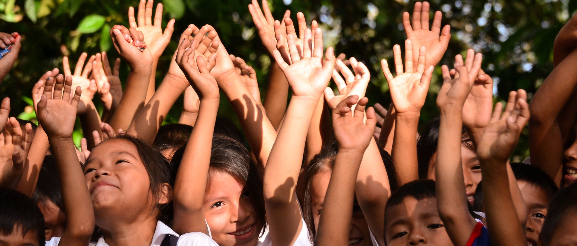 Crowd of smiling children with hands in the air reaching up to the sky