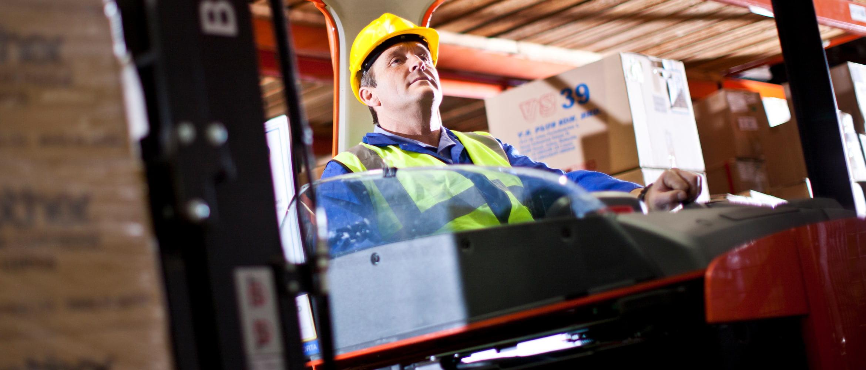 Workman operates a crane in a warehouse