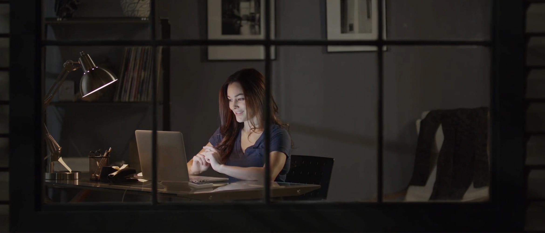Ženska zvečer sedi za mizo s prenosnim računalnikom