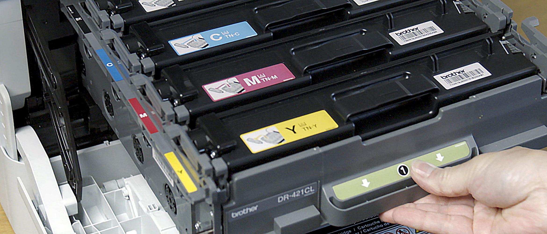 moški odpira tiskalnik s tonerji