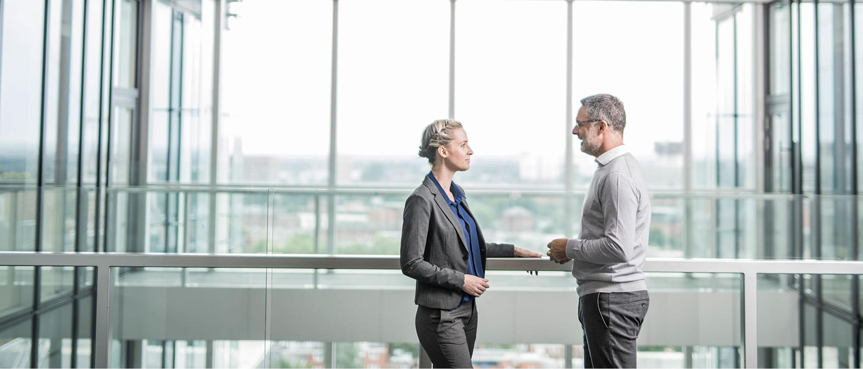 Poslovni moški in ženska se srečata na balkonu pisarne