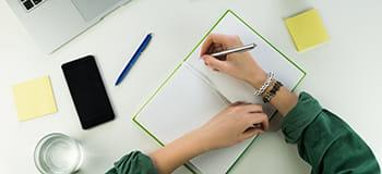 pisanje v zvezek na mizi z vidnim mobilnim telefonom