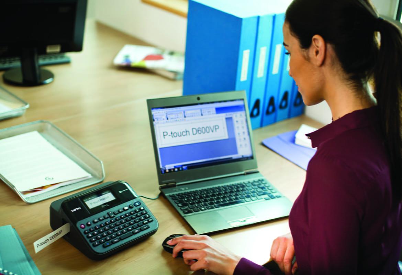 Ženska s čopom uporablja tiskalnik nalepk Brother PT-D600