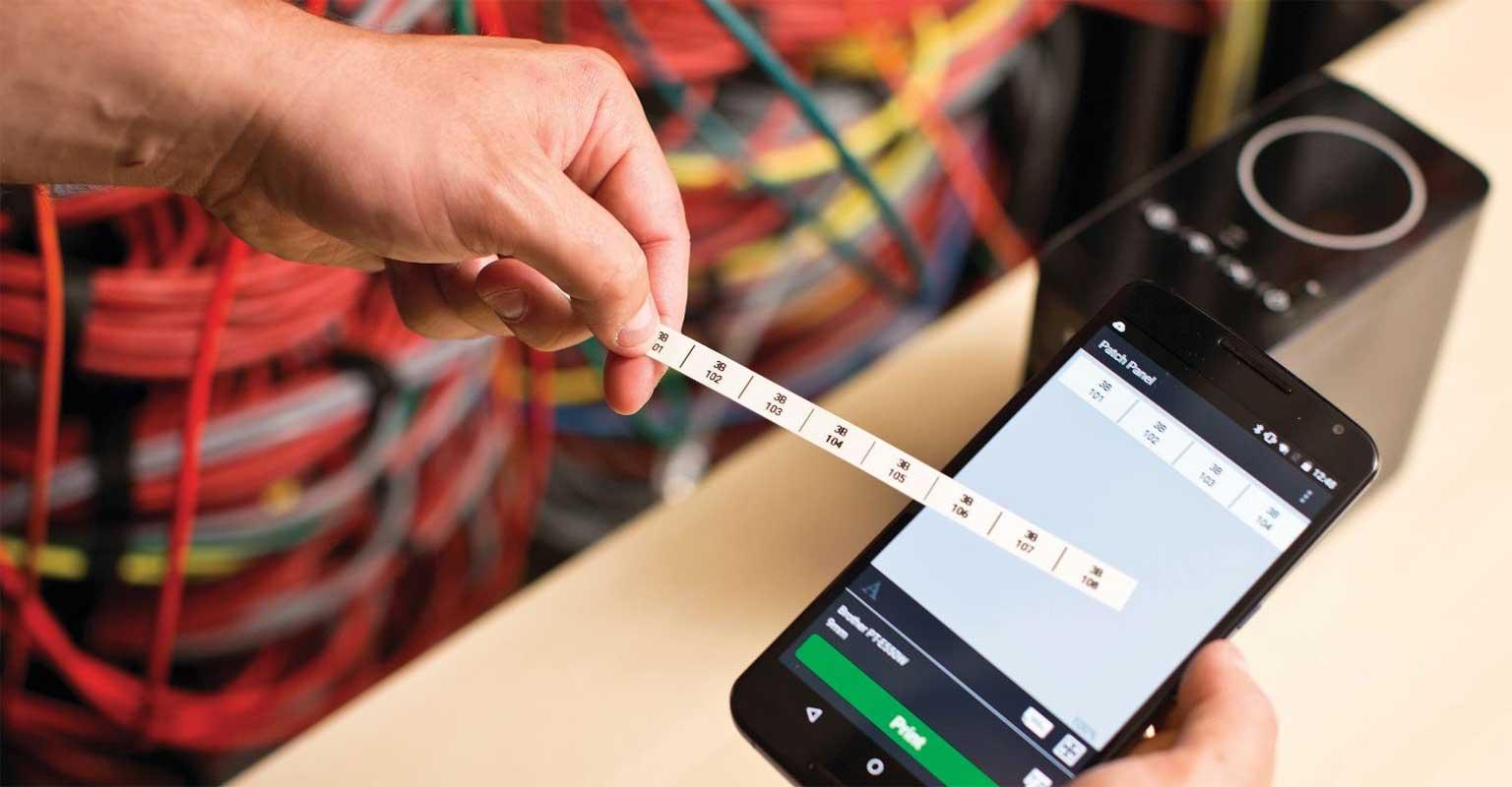 Aplikacija Cable Label Tool na pametnem telefonu z natisnjeno nalepko na Brother P-touch