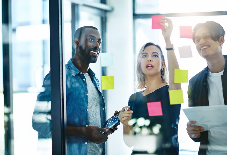 Trije pisarniški delavci v trenutku kreativnega sodelovanja med poslovnim srečanjem prilepijo na stekleno steno nalepke s sporočilom