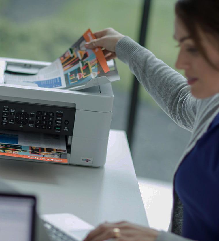Ženska sedi za mizo in vzame dokument iz tiskalnika