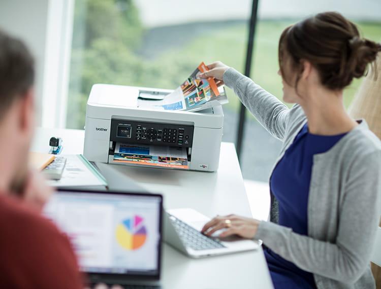 Ženska v modri majici in sivi jopici poleg tiskalnika v domači pisarni