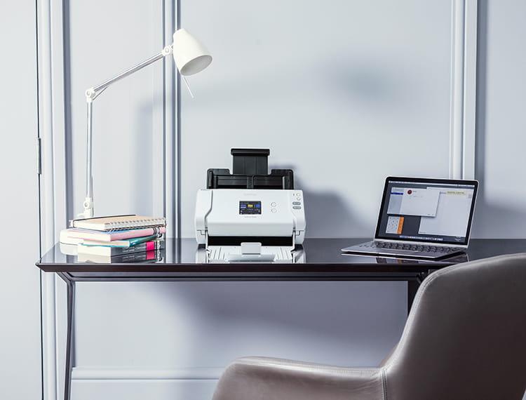 Brother skener na leseni pisarniški mizi z belo svetilko in prenosnikom