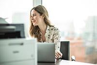 Ženska sedi za mizo, na kateri sta prenosni računalnik in tiskalnik