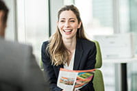 Ženska sedi v pisarni z barvnim tiskalnikom v ozadju in se smehlja