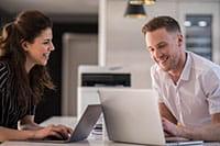 Man and woman sat at desk with printer between them in background Moški in ženska sedita za mizo s tiskalnikom v ozadju