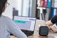 Ženska z očali oblikuje nalepke na P-touch Cube Plus prek računalnika