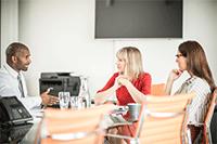 2 ženski in moški so se usedli za mizo