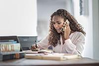 Ženska z dolgimi lasmi govori po telefonu