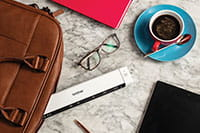 Brother DS-640 mobilni dokumentni skener, očala, kava, usnjena torba za prenosnik, svinčnik, tablica, roza zvezek