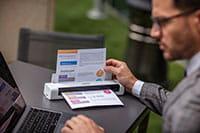 Moški v sivi obleki z očali sedi na prostem s prenosnikom in mobilni skener dokumentov Brother DSmobile DS740D z barvnim dokumentom A4
