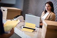 Ženska z rjavimi lasmi na recepciji s prenosnikom uporablja mobilni skener dokumentov Brother DSmobile DS740D, škatle, dostavljavec, mapa s sponko