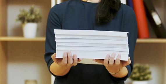 Ženska drži kup papirja